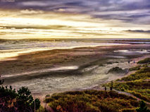Clouds and surf. A cold winter cloudy sky over the long waves of a sandy beach on the Oregon coast Stock Photography