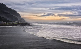 Clouds and surf. A cold winter cloudy sky over the long waves of a sandy beach on the Oregon coast Royalty Free Stock Photography