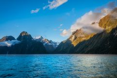 Clouds surrounding the mountain cliffs at Milford Sound, NZ. Beautiful View of Milford Sound`s sheer cliffs surrounded by clouds close to sunset in Fiordland Stock Image