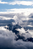 Clouds surrounding rocky mountain peak. White billowy clouds hugging rocky mountain peak against blue skies on sunny day Royalty Free Stock Image