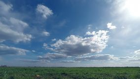 Clouds sweep over the green field stock video footage