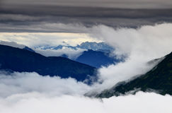 Clouds swirling around and above Carnic and Julian Alps. Clouds swirling around and above the ridges of Carnic Alps and Julian Alps in the background, Friuli Stock Photo