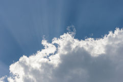 Clouds taking a blue sky lit by the sun casting rays from behind. The clouds Stock Images