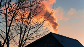 Clouds of thick smoke from the chimney at sunset house Stock Photos