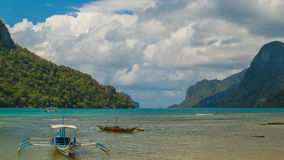 Clouds timelapse in the beautiful beach of El Nido, Palawan. Clouds timelapse and tourist boat in the beautiful tropical beach landscape at summer stock video footage