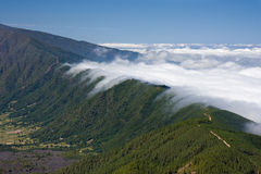 Clouds tumbling over a mountain ridge at La Palma. Canary Islands, Spain royalty free stock photo