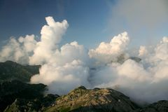 Clouds under mountains stock photo