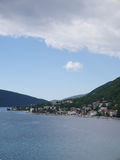 Town on coast line, on hills, under clouds and sky. Royalty Free Stock Photography