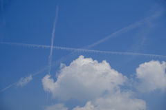 Clouds and vapour trails. White cumulus clouds and vapour trails crossing beautiful blue sky Stock Image