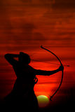 Clouds of War. A silhouette of an archer aiming at the enemy at sunrise during an ancient war. A metaphorical image showing high aims or achievement Royalty Free Stock Photo