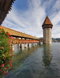 Clouds in water. Lake in Lucerne with a tower and a bridge, decorated with flowers stock photography