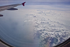 Clouds and wing through airplane window. Thailand stock photo