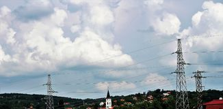 Clouds, wires and church. At the spring day Stock Images