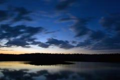Cloudscape över laken på skymningen Arkivbild