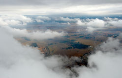 Cloudscape. African landscape from above while descending through clouds Stock Photos