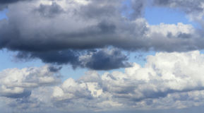 Cloudscape. Clouds, both dark and light, almost entirely covering the blue sky beyond stock images