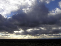Cloudscape. Multiple rays of sunlight burst through dark clouds over the Nevada landscape Stock Images