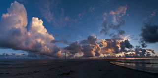 Cloudscape above the coast. Panorama of a cloudscape above the coast of the Wadden Sea Stock Photos