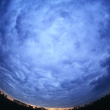 Cloudscape background. Dramatic sky view through the super wide angle lens Royalty Free Stock Photo