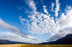 Cloudscape in blue. Wide angle shot of a blue sky and distant mountains with coastal marshes in the foreground Royalty Free Stock Photography