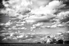 Cloudscape con il mulino a vento e l'azienda agricola, coltivanti Case del cottage e del mulino sul campo verde, agricoltura paes Fotografia Stock