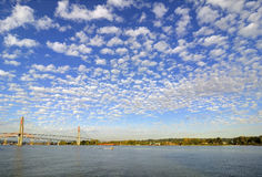 Cloudscape with cotton-like clouds up in the blue sky and over the river Royalty Free Stock Photo