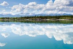 Cloudscape del yermo de Yukon reflejado en el lago tranquilo Imagenes de archivo