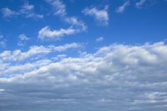 Cloudscape image with blue sky and white fluffy clouds. Background royalty free stock image