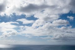 Cloudscape mot blå solig himmel ovanför havet Royaltyfri Bild