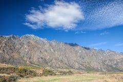 Cloudscape nad góra i zieleni pole Obrazy Stock