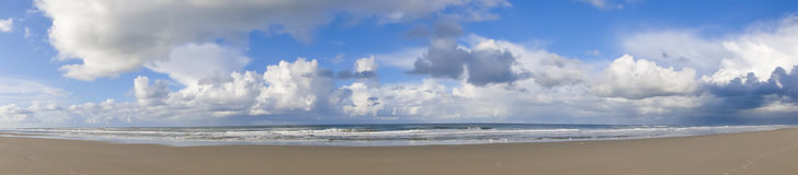 Cloudscape over beach. Panoramic view of cloudscape and blue sky over picturesque beach with sea in background Royalty Free Stock Photos