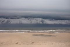 Cloudscape over beach. Scenic view of dark low level cloudscape over ocean beach Royalty Free Stock Photo