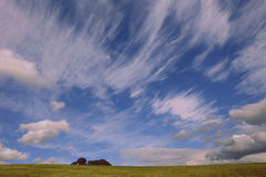 Cloudscape over green field Royalty Free Stock Image