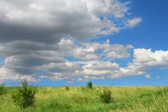 Cloudscape over green field Royalty Free Stock Images