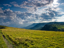 Cloudscape over mountains. Scenic view of cloudscape over mountains with field in foreground Stock Photos