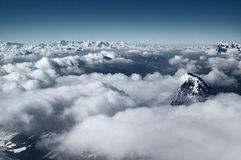 Cloudscape over mountains. Aerial view of snow capped mountain peaks protruding above cloudscape with blue sky background, Dachstein, Austria stock photo