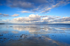 Cloudscape over North sea. Cloudscape reflected in water of North sea by Moddergat, Netherlands Royalty Free Stock Images