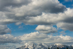 Cloudscape over snow covered mountains Stock Image