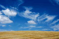 Cloudscape over straw field. Scenic view of blue sky and cloudscape over corn or straw field in countryside royalty free stock image