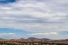 Cloudscape para fora sobre o deserto e os mesas de New mexico com uma fábrica de tratamento do gás no primeiro plano imagens de stock royalty free