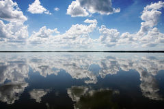 Cloudscape reflecting on blue sea. Scenic view of blue sky and cloudscape reflecting on calm sea Stock Photos