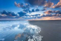 Cloudscape reflekterade i havet på soluppgång Arkivfoto