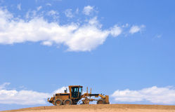 Cloudscape and road grader. Scenic view of road grader on construction site under beautiful cloudscape Royalty Free Stock Photography