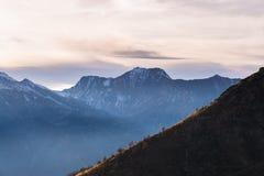 Cloudscape scenico sopra catena montuosa maestosa al tramonto Fotografie Stock Libere da Diritti