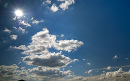 Cloudscape and sun agains a blue sky Royalty Free Stock Photography