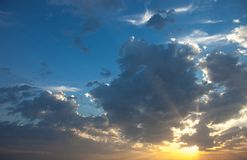 Cloudscape with the sun rays radiating from behind the cloud Royalty Free Stock Image
