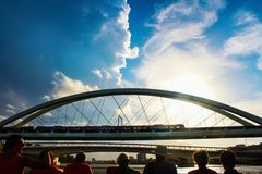 Cloudscape and sun shining on train crossing Brisbane River with silhouettes of people watching it from ferry in foreground royalty free stock images