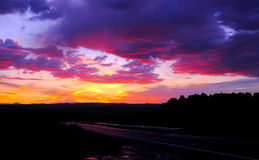 Cloudscape at Sunset. Vibrant cloudscape at sunset with vivid colors of orange, pink, yellow, red and purple with dramatic dark clouds Royalty Free Stock Photo