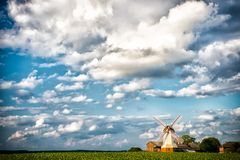 Cloudscape with windmill and farm, farming. Mill and cottage houses on green field, agriculture. Rural landscape on cloudy blue sk. Y, vacation. Summer vacation Royalty Free Stock Photo