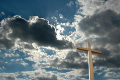 Cloudscape and wooden cross. Tall wooden cross with blue sky and dark cloudscape background stock photo
